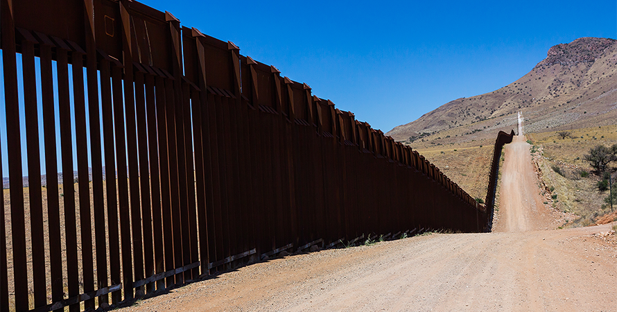u.s.-mexico border fence runs along a dirt road
